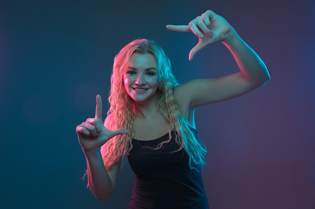 Caucasian young woman's portrait on gradient background in neon light. beautiful female model with unusual look. concept of human emotions, facial expression, sales, ad. smiling cute.