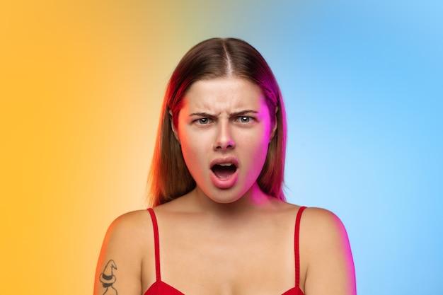 Caucasian young woman's portrait on gradient in neon