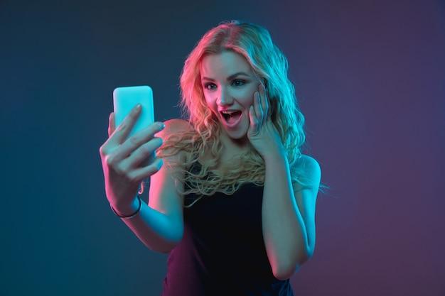 Портрет молодой женщины кавказа на фоне градиента в неоновом свете. красивая женская модель с необычным внешним видом. понятие человеческих эмоций, выражения лица, продаж, рекламы. делаем селфи, делаем ставки, покупки.