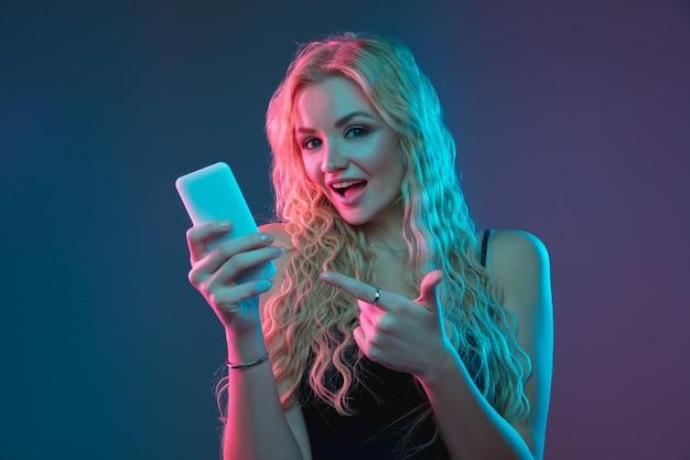 ネオンの光のグラデーションの背景に白人の若い女性の肖像画。珍しい表情の美しい女性モデル。人間の感情、顔の表情、販売、広告の概念。自撮り、賭け、購入。