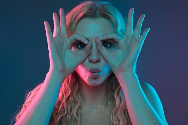 Портрет молодой женщины кавказа на фоне градиента в неоновом свете. красивая женская модель с необычным внешним видом. концепция человеческих эмоций, выражения лица, продаж, рекламы. указывая, улыбаясь. copyspace.
