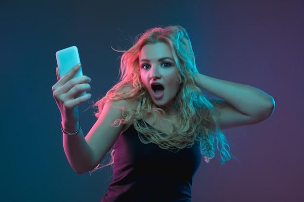 ネオン光の勾配空間での白人の若い女性の肖像画。変わった表情の美しい女性モデル