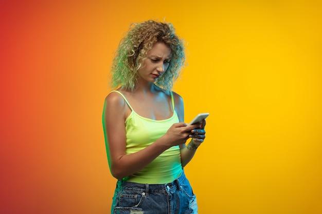 Портрет кавказской молодой женщины на градиентном студийном фоне в неоне