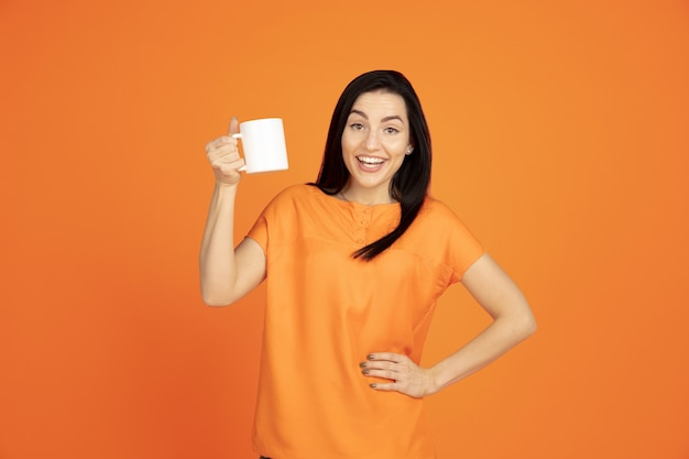 オレンジ色のスタジオの背景に白人の若い女性の肖像画。シャツの美しい女性ブルネットモデル。人間の感情、表情、販売、広告の概念。コピースペース。コーヒーやお茶を飲む。