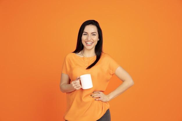 Портрет молодой женщины кавказа на оранжевом фоне студии. красивая женская модель брюнет в рубашке. понятие человеческих эмоций, выражения лица, продаж, рекламы. copyspace. пить кофе или чай.