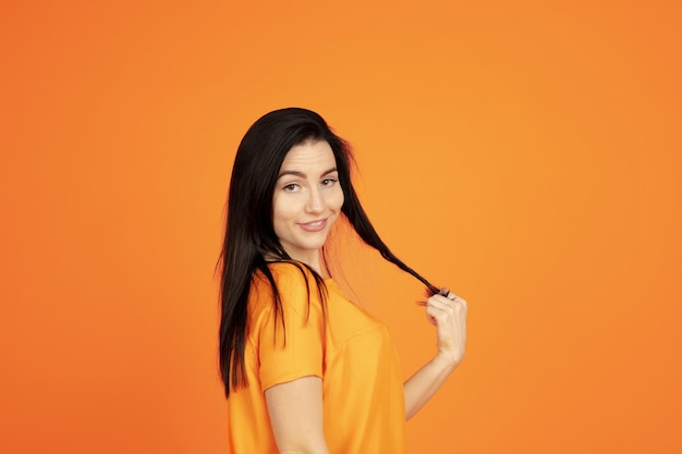 オレンジ色のスタジオの背景に白人の若い女性の肖像画。シャツの美しい女性ブルネットモデル。人間の感情、顔の表情、販売、広告の概念。コピースペース。かわいく見えて、笑っています。