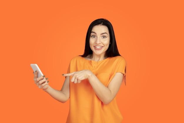 Портрет молодой женщины кавказа на оранжевом фоне студии. красивая женская модель брюнет в рубашке. понятие человеческих эмоций, выражения лица, продаж, рекламы. copyspace. делаем селфи, выигрываем в ставке.