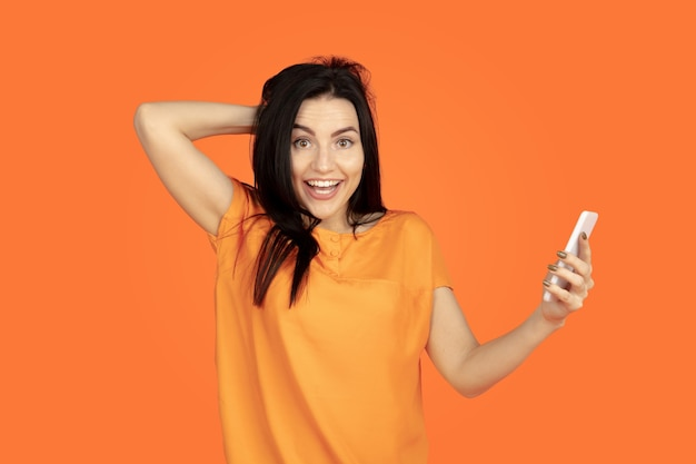 オレンジ色のスタジオの背景に白人の若い女性の肖像画。シャツの美しい女性ブルネットモデル。人間の感情、顔の表情、販売、広告の概念。コピースペース。自撮り写真を作って、賭けに勝ちましょう。