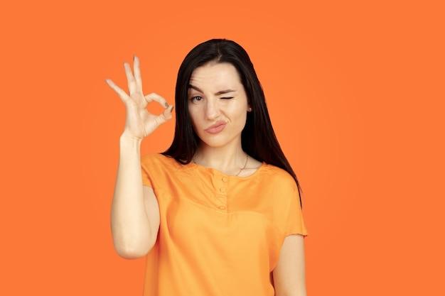 オレンジ色のスタジオの背景に白人の若い女性の肖像画。シャツの美しい女性ブルネットモデル。人間の感情、顔の表情、販売、広告の概念。コピースペース。 okのサインを表示しています。