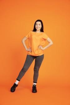 オレンジ色のスタジオの背景に白人の若い女性の肖像画。シャツの美しい女性ブルネットモデル。人間の感情、表情、販売、広告の概念。コピースペース。立って笑っている。
