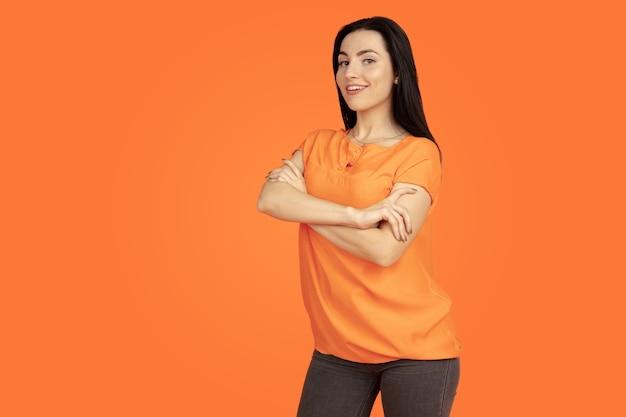 オレンジ色のスタジオの背景に白人の若い女性の肖像画。シャツの美しい女性ブルネットモデル。人間の感情、顔の表情、販売、広告の概念。コピースペース。立っている手が交差した。