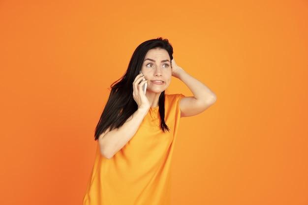 오렌지 스튜디오 배경에 백인 젊은 여자의 초상화. 셔츠에 아름 다운 여성 갈색 머리 모델입니다. 인간의 감정, 표정, 판매, 광고의 개념. copyspace. 전화 통화.