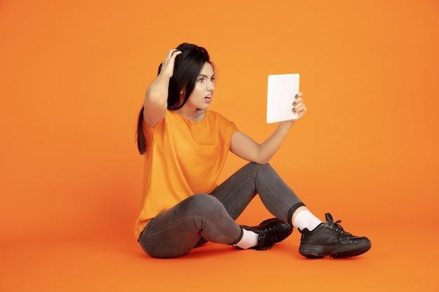 Портрет молодой женщины кавказа на оранжевом фоне студии. красивая женская модель брюнет в рубашке. концепция человеческих эмоций, выражения лица, продаж, рекламы. copyspace. использование планшета, ведение видеоблога.