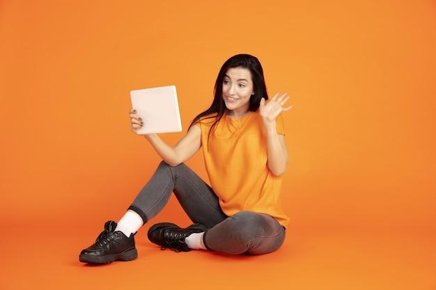 Портрет молодой женщины кавказа на оранжевом фоне студии. красивая женская модель брюнет в рубашке. понятие человеческих эмоций, выражения лица, продаж, рекламы. copyspace. использование планшета, ведение видеоблога.