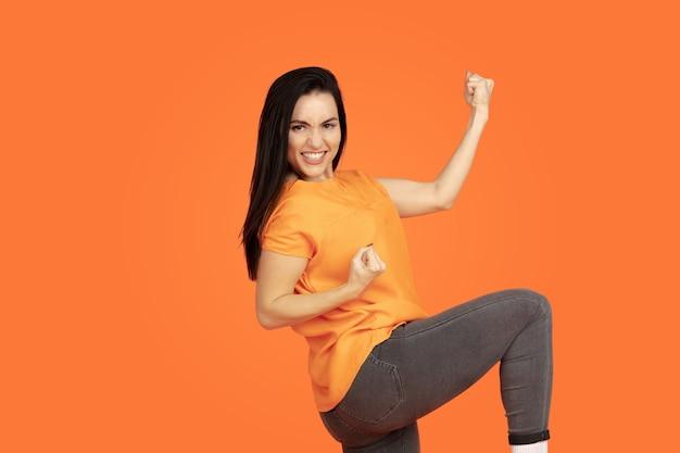 オレンジ色のスタジオの背景に白人の若い女性の肖像画。シャツの美しい女性ブルネットモデル。人間の感情、顔の表情、販売、広告の概念。コピースペース。笑いながら勝者のように勝ちなさい。