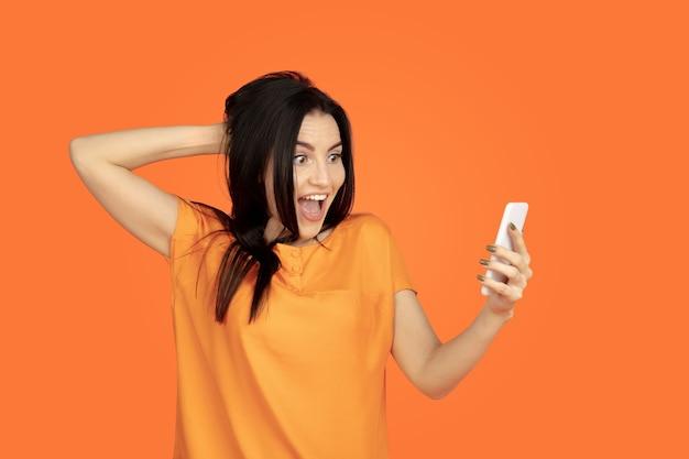 オレンジ色のスタジオで白人の若い女性の肖像画