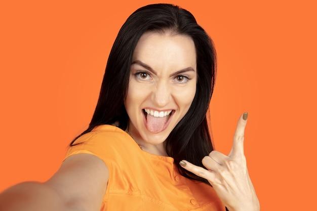 オレンジ色の壁に白人の若い女性の肖像画