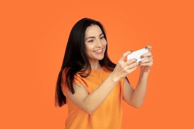 Ritratto di giovane donna caucasica su sfondo arancione