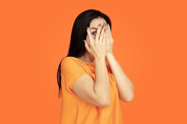 Caucasian young woman's portrait on orange background