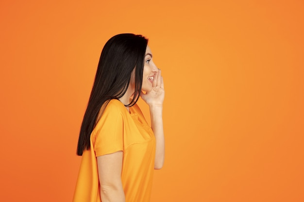Caucasian young woman's portrait on orange background