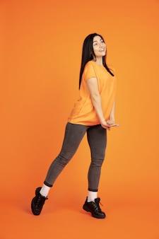 Ritratto di giovane donna caucasica su sfondo arancione studio. bello modello femminile del brunette in camicia. concetto di emozioni umane, espressione facciale, vendite, annuncio. copyspace. ballando, ridendo.