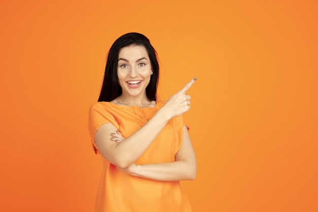 Ritratto di giovane donna caucasica su sfondo arancione studio. bello modello femminile del brunette in camicia. concetto di emozioni umane, espressione facciale, vendite, annuncio. copyspace. indicare, mostrare, sorridere.