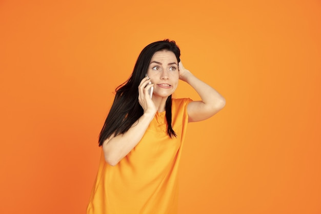 Caucasian young woman's portrait on orange studio background. beautiful female brunette model in shirt. concept of human emotions, facial expression, sales, ad. copyspace. talking on phone.
