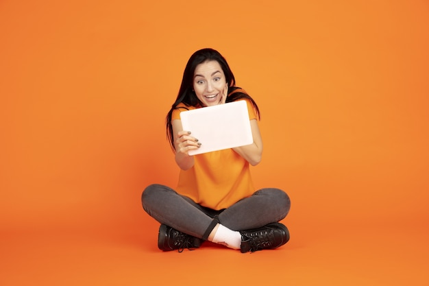 Caucasian young woman's portrait on orange studio background. beautiful female brunette model in shirt. concept of human emotions, facial expression, sales, ad. copyspace. using tablet, vlogging.