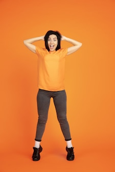 Caucasian young woman's portrait on orange studio background. beautiful female brunette model in shirt. concept of human emotions, facial expression, sales, ad. copyspace. winning, crazy happy.