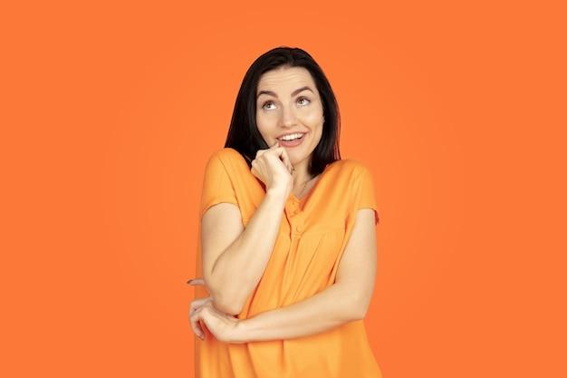 Ritratto di giovane donna caucasica su sfondo arancione studio.