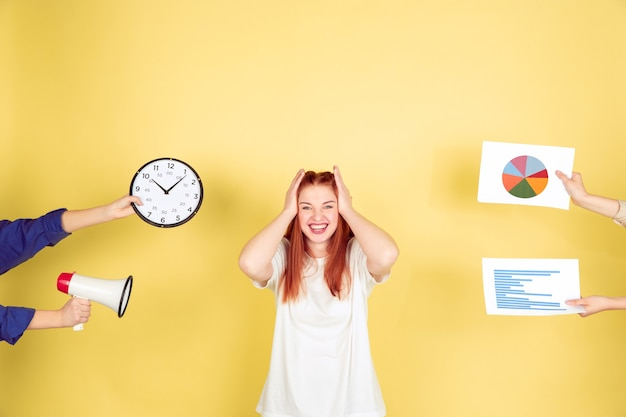Ritratto della giovane donna caucasica su sfondo giallo, troppi compiti