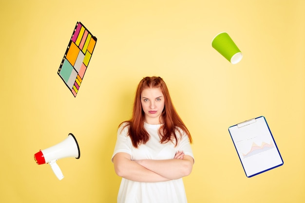 Caucasian young woman's portrait on yellow background, too much tasks
