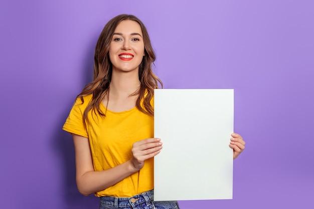 Кавказская молодая женщина улыбается и держит пустой плакат в желтой футболке, изолированной на сиреневом фоне в студии. мокап для дизайна