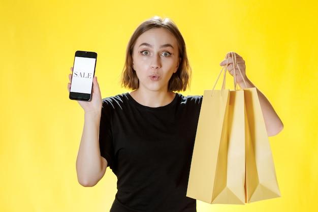 Кавказская молодая женщина улыбается и держит мобильный телефон, а также торговый пакет и смотрит в экран телефона.