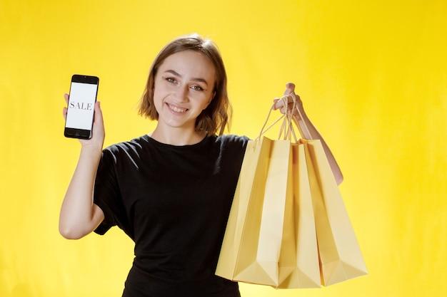 Кавказский молодая женщина улыбается и держит мобильный телефон, и пакет покупок и смотрит в экран телефона.