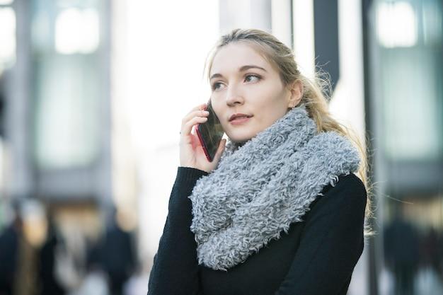耳にスマートフォンで誰かと話している白人の若い女性