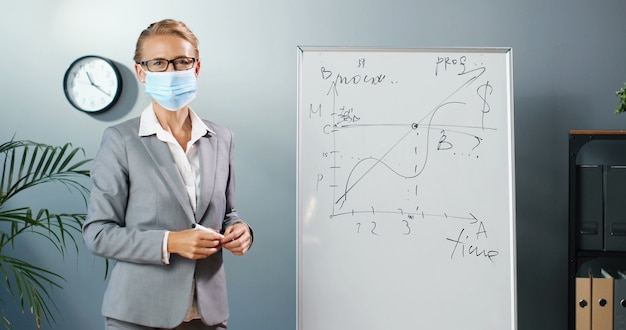 Caucasian young woman teacher in medical mask at school writing formulas and mahematics laws on blackboard. school concept. female math lecturer in glasses explaining physics laws. education. covid-19