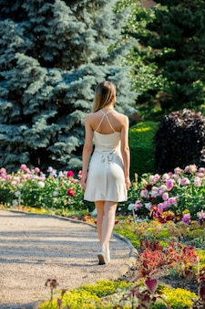 庭の花と路地を歩いている白人の若い女性