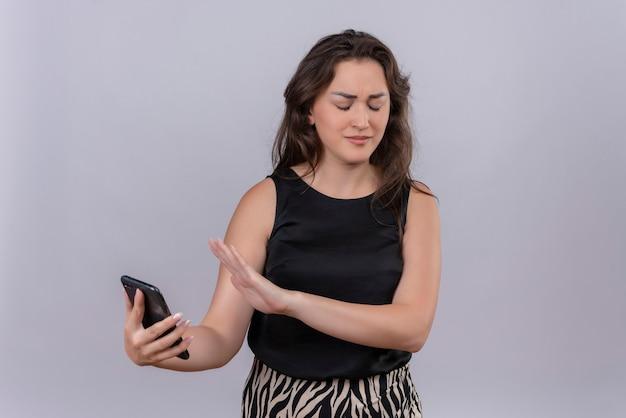 La giovane donna caucasica che porta la maglietta nera non vuole sguardi un telefono sulla parete bianca