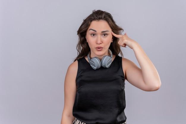 La giovane donna caucasica che porta la maglietta nera in cuffie ha messo il dito sulla fronte sul muro bianco