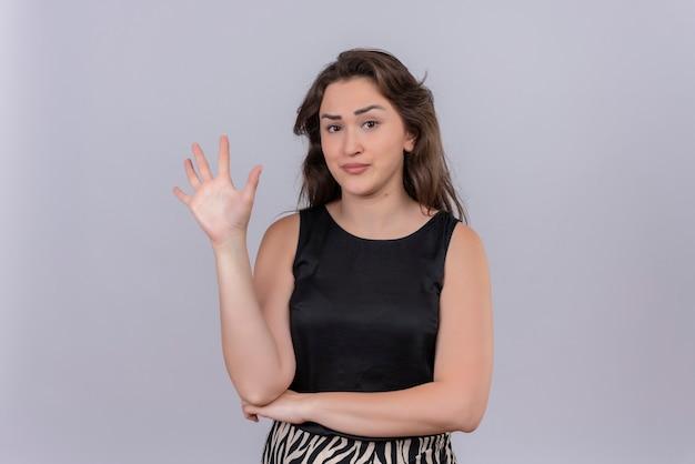 白い壁に黒いアンダーシャツを着ている白人の若い女性