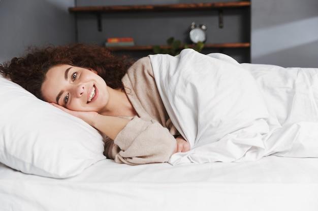 집에서 흰색 침대 시트에 침대에서 자고 집 옷을 입고 백인 젊은 여자