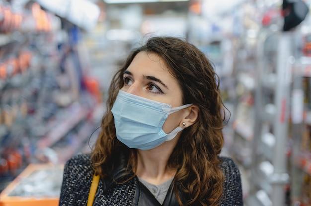 Кавказская молодая женщина в защитной маске делает покупки в магазине.