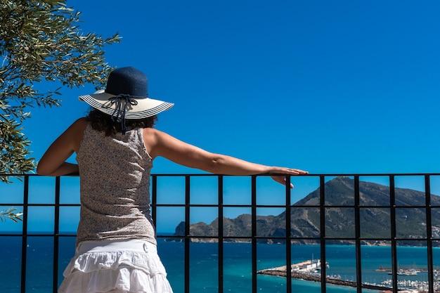 난간에 기대어 그녀의 뒤에 여름 옷과 모자와 백인 젊은 여자