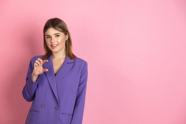 Портрет кавказской молодой женщины на розовом студийном фоне эмоциональный и выразительный