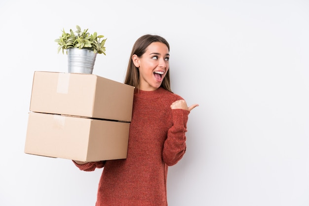 Молодая женщина caucasic, держащая коробки, изолировала пункты с большим пальцем палец, смеющийся и беззаботный.