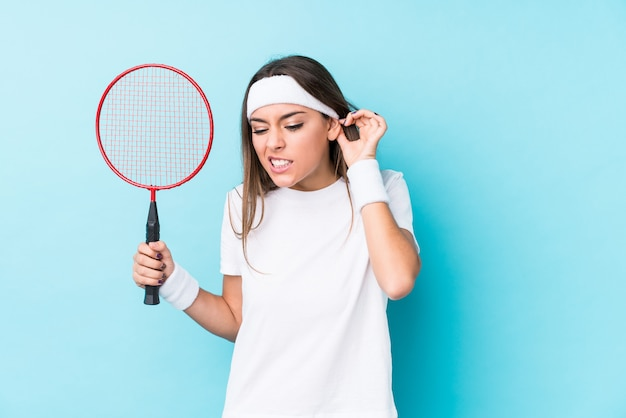 Молодая женщина caucasic играя бадминтон изолировала покрывать уши руками.