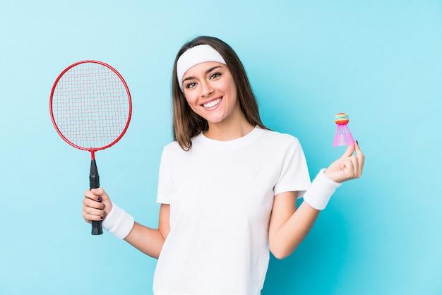 Молодая женщина caucasic играя бадминтон изолировала счастливый, усмехаться и жизнерадостный.