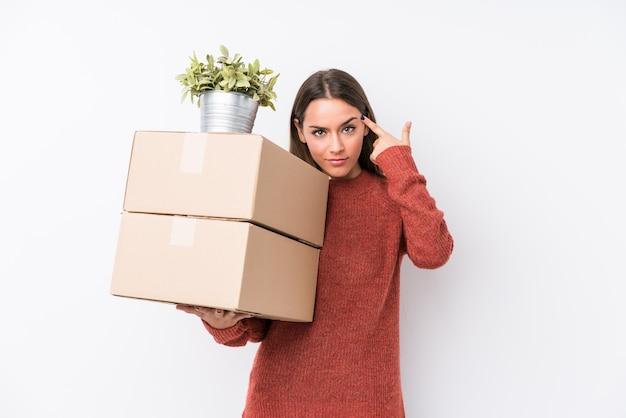 Молодая женщина caucasic держа коробки изолировала указывать висок с пальцем, думая, сфокусированный на задаче.