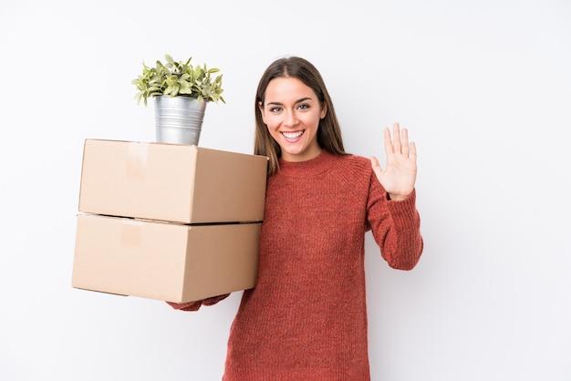 Молодая женщина caucasic держа коробки усмехаясь жизнерадостный показывая номер пять с пальцами